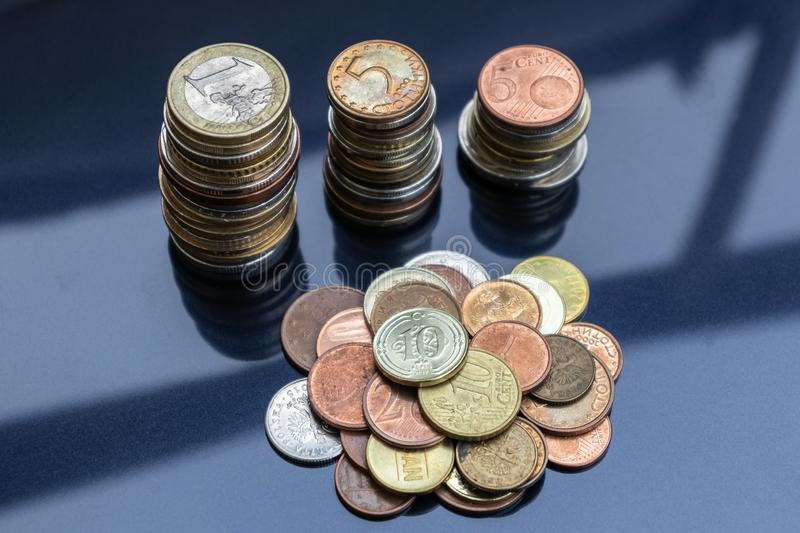A small mountain of coins from different countries and three towers of coins. royalty free stock photo