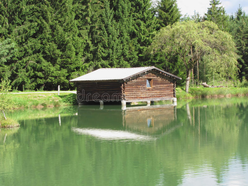Small mountain lake with house over water and forest background . Fie allo sciliar, South Tyrol, Italy.  royalty free stock images
