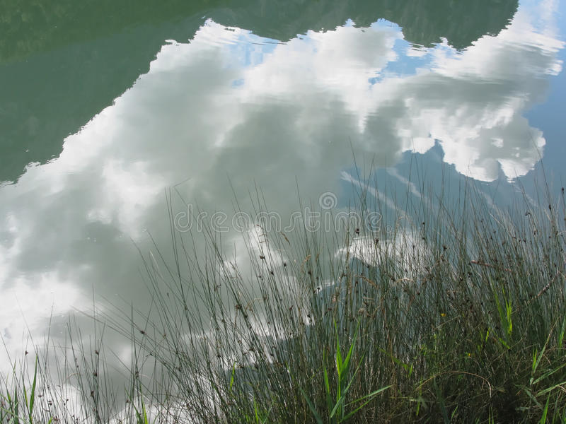 Small mountain lake with reflections of clouds. Fie allo sciliar, South Tyrol, Italy.  stock photography