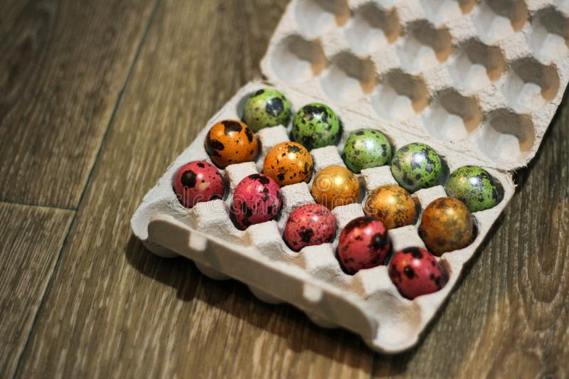 Small multi-colored testicles in a box. three colors - green, red and orange. a box on a floor royalty free stock photography