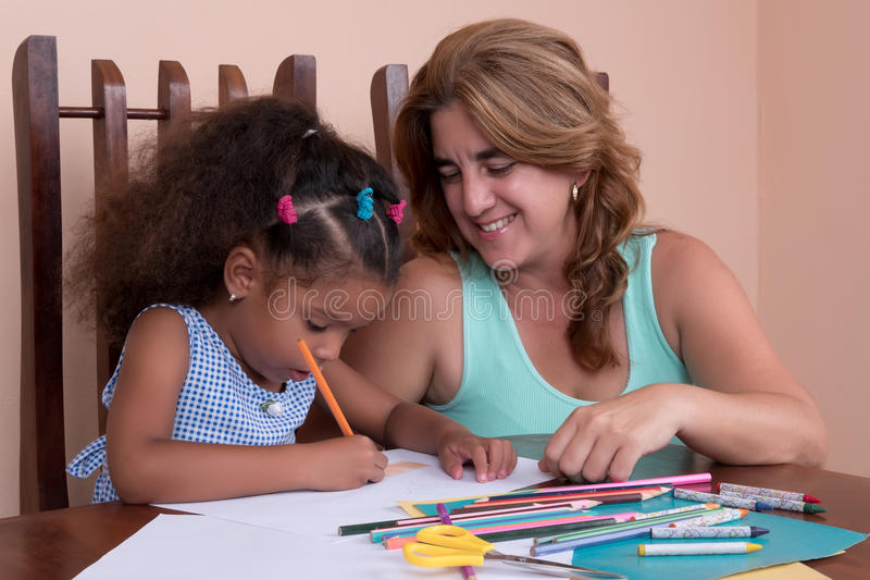 Small multiracial girl and her mother drawing with color pencils stock images