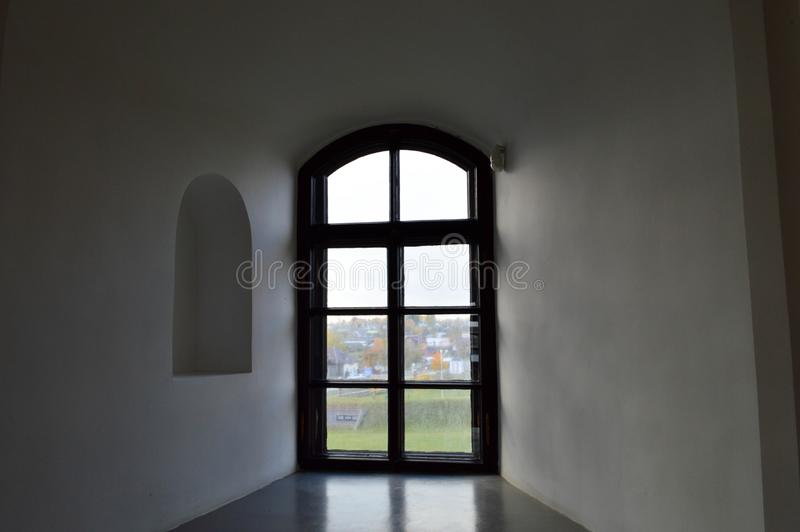 A small narrow black window with a frame on an old ancient stone white thick concrete wall in an old castle. The background stock photo