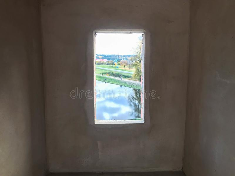 A small narrow black window with a frame on an old ancient stone white thick concrete wall in an old castle. The background stock photography