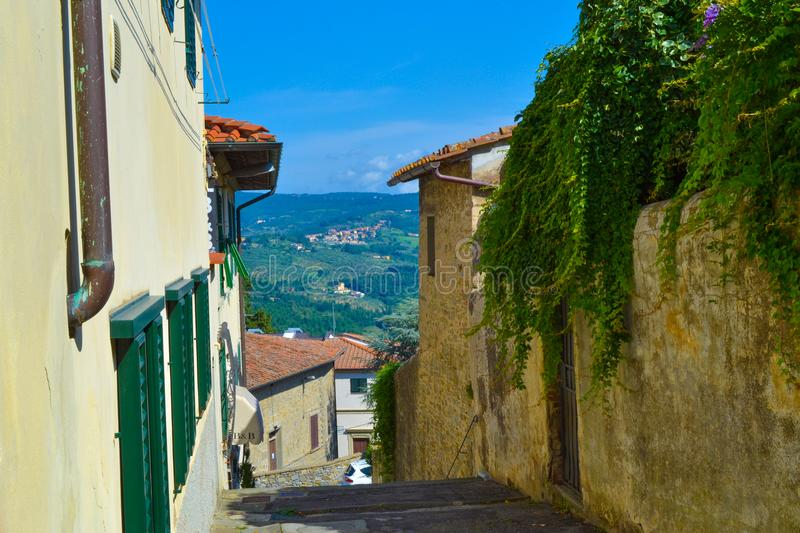 Small, narrow and colored street in Fiesole, Italy. Small, narrow and colored street with Tuscany fields at background in Fiesole, Italy stock photo