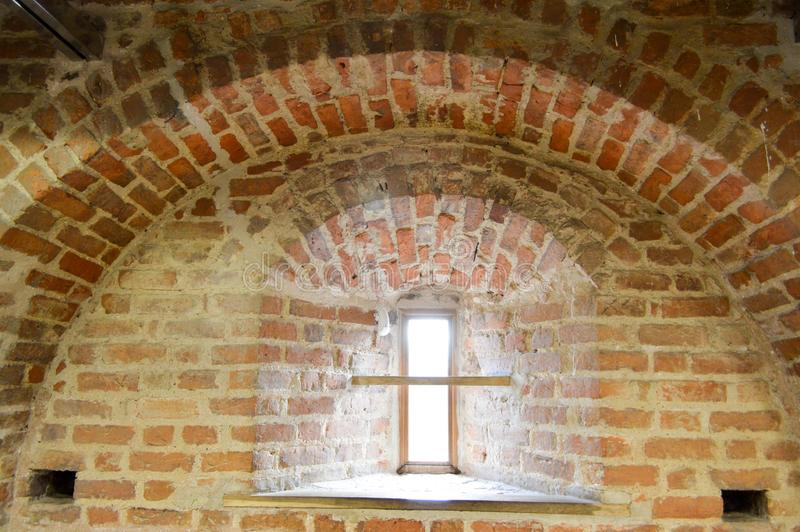 A small narrow window on an old, ancient, cracked stone shabby brick wall of red brick in the basement. The background royalty free stock photography