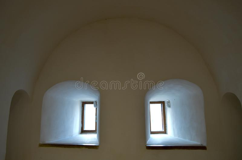 Small narrow windows with an arch on an old ancient stone thick wall in the basement, an old castle. The background stock images