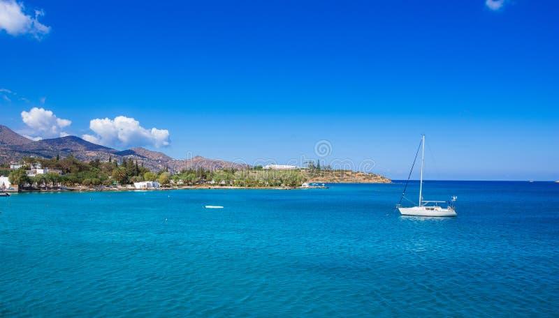 Small natural harbor with anchored sailing boat, Agios Nikolaos, Crete. Small natural harbor with anchored sailing boat, Agios Nikolaos, Crete, Greece royalty free stock photos