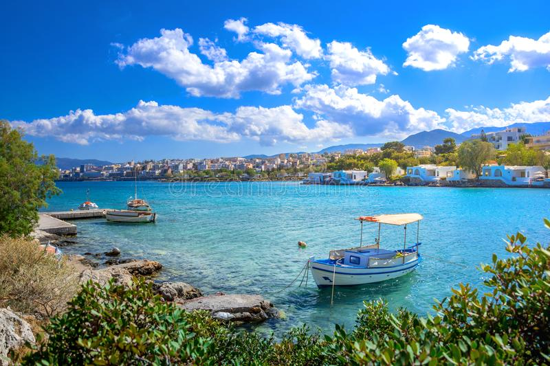 Small natural harbor with anchored sailing boat, Agios Nikolaos, Crete. Small natural harbor with anchored fishing boats with the beautiful town of Agios stock photography