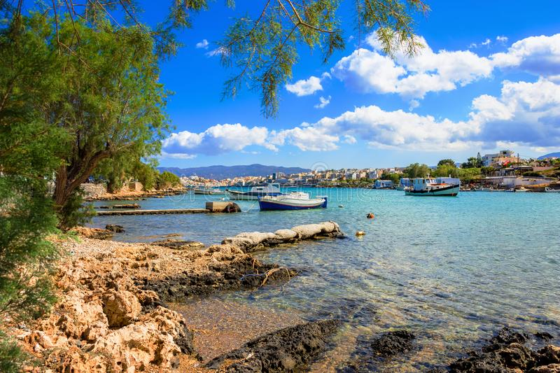 Small natural harbor with anchored sailing boat, Agios Nikolaos, Crete. Small natural harbor with anchored fishing boats with the beautiful town of Agios royalty free stock images