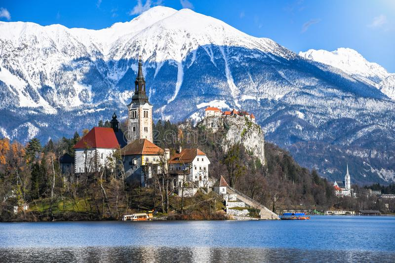 Small natural island in the middle of alpine lake with church dedicated to assumption of Mary and castle with snowy mountains stock photo