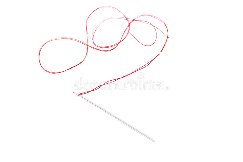 Small needle with thread isolated over the white background. Small needle with red thread isolated over the white background stock photo