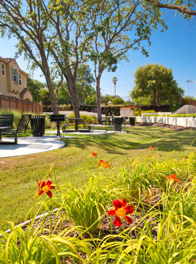 Small Neighborhood Park. With red flowers, plants, green grass, black metal tables and chairs, and barbecue grills. Trees and blue sky stock images