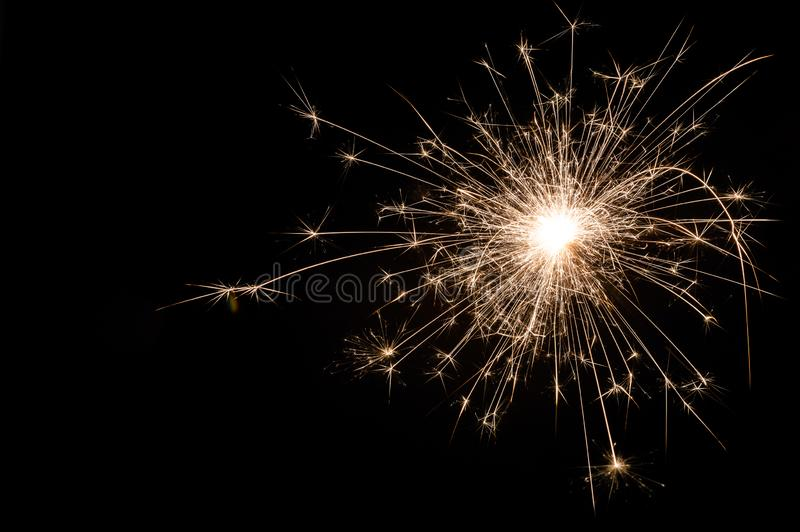 Small new year sparkler on black background stock photography