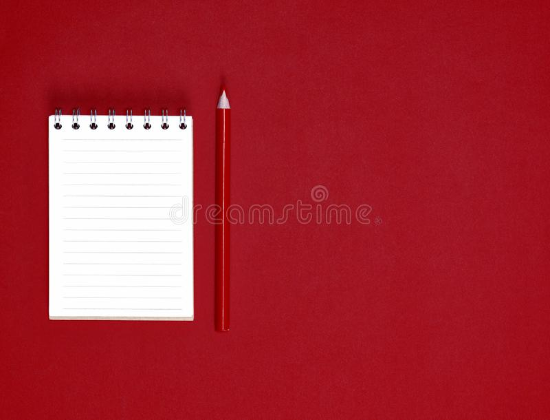 Small notebook with empty white sheets in line and red wooden pencil, red background. Empty space stock image