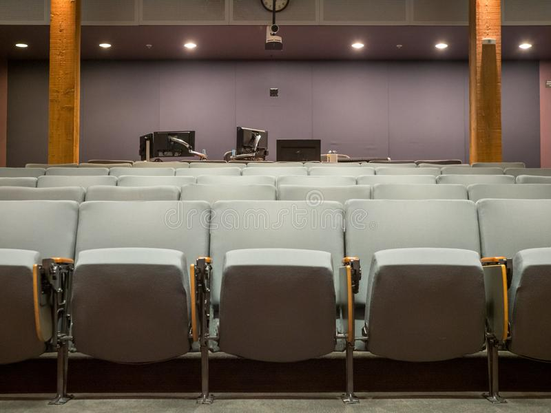 Small office auditorium with gray chairs and computer monitor set up in rear royalty free stock photography