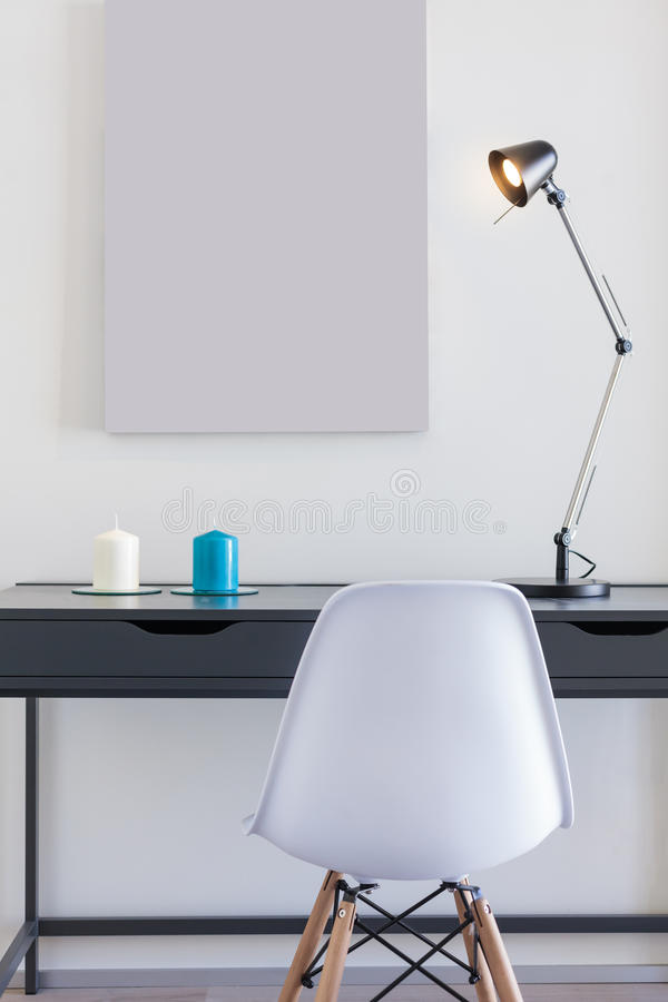 Small office desk with white chair and single lamp. Small office desk with white chair and lamp stock image