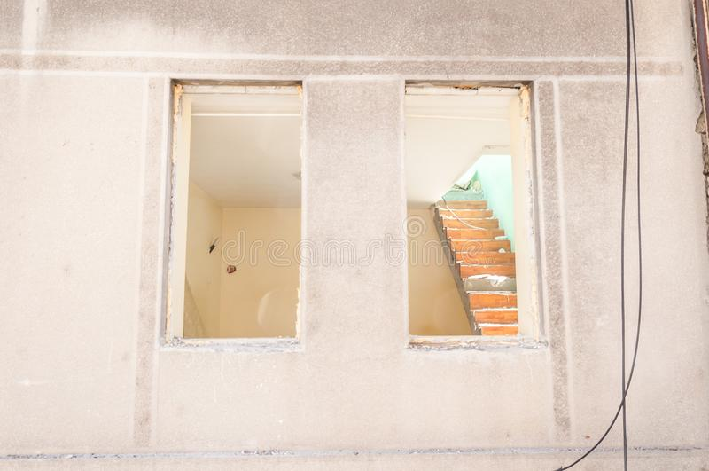 Small old and abandoned damaged house cracked windows without roof demolished by the earthquake destruction closeup stock image