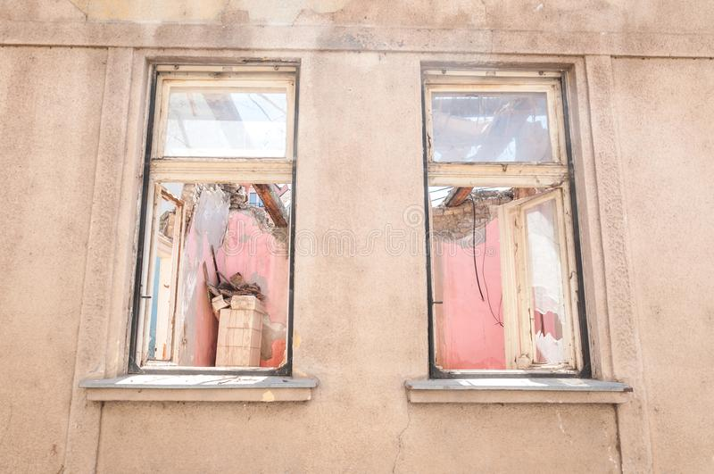 Small old and abandoned damaged house cracked windows without roof demolished by the earthquake destruction closeup stock photo