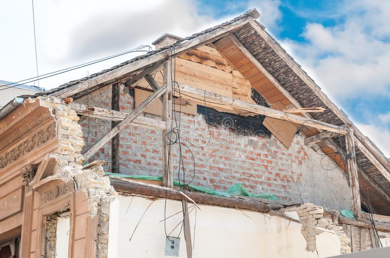 Small old and abandoned house roof demolished by the earthquake destruction closeup with blue sky above royalty free stock image