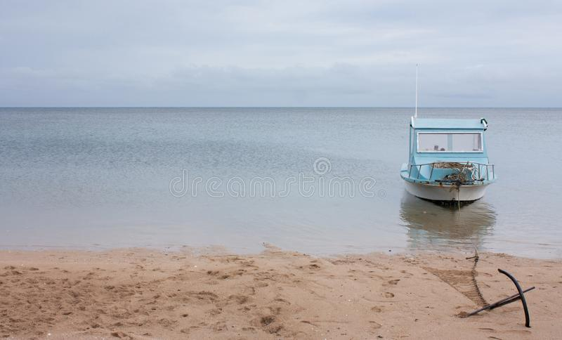 A small old boat with an anchor at a beach in Tonga royalty free stock photography
