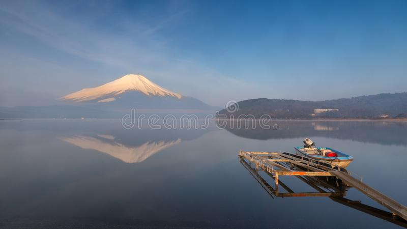 A small old boat at a port with beautiful water reflection of Fuji mountain at Yamanaka lake stock photo