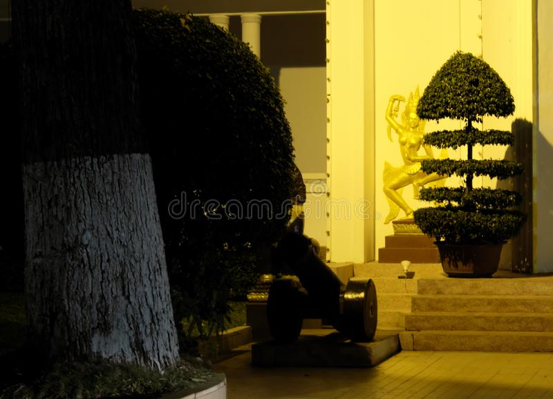 A small old cannon, standing near the entrance to the building. Topiary. Night scene.  royalty free stock image