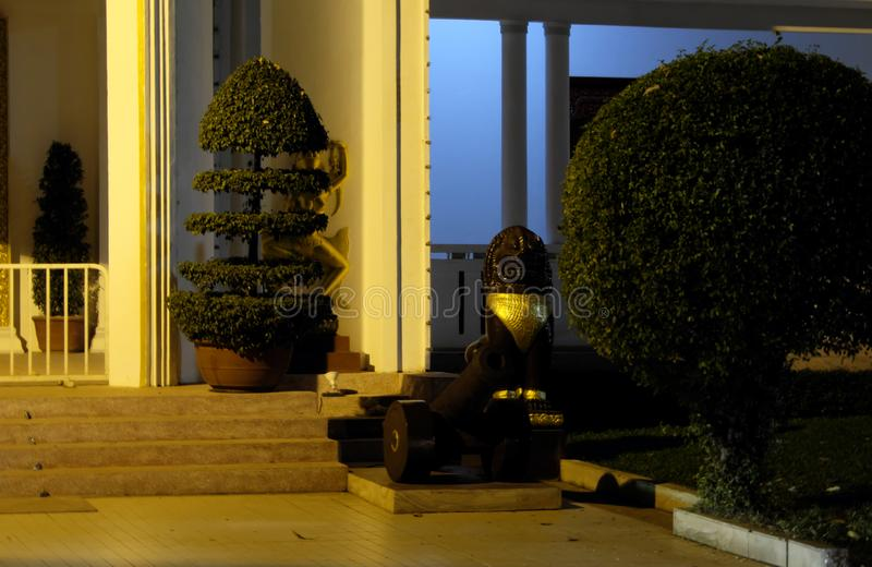 A small old cannon, standing near the entrance to the building. Topiary. Night scene.  stock photography