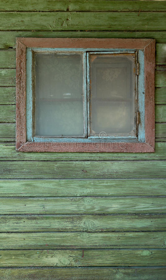 A small old closed window in green rustic wooden wall of an old house stock photos