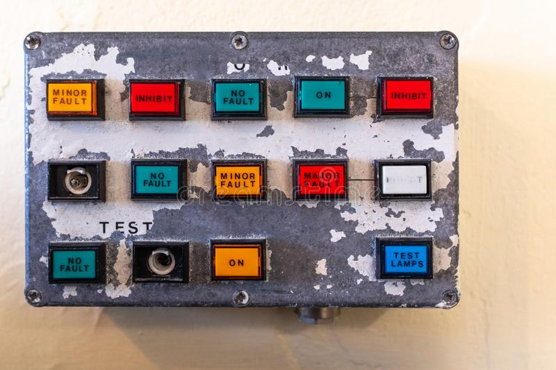 A small old control panel showing buttons of various colours on old paint peeling panel stock image