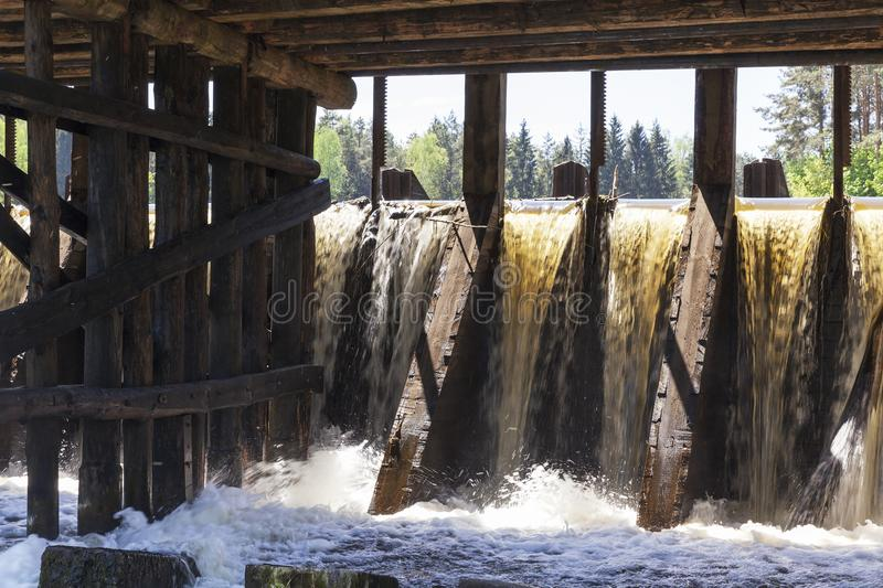 Small old dam. A small old dam on the lake, made of wooden parts, a closeup of a waterfall stock images