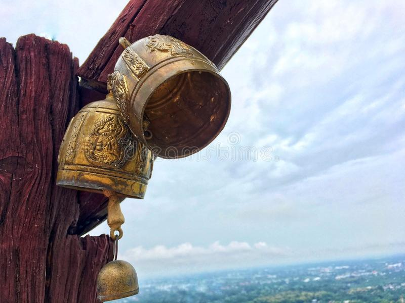 Small old golden bell hang on wooden swing pole at temple in front of rural view. royalty free stock photography