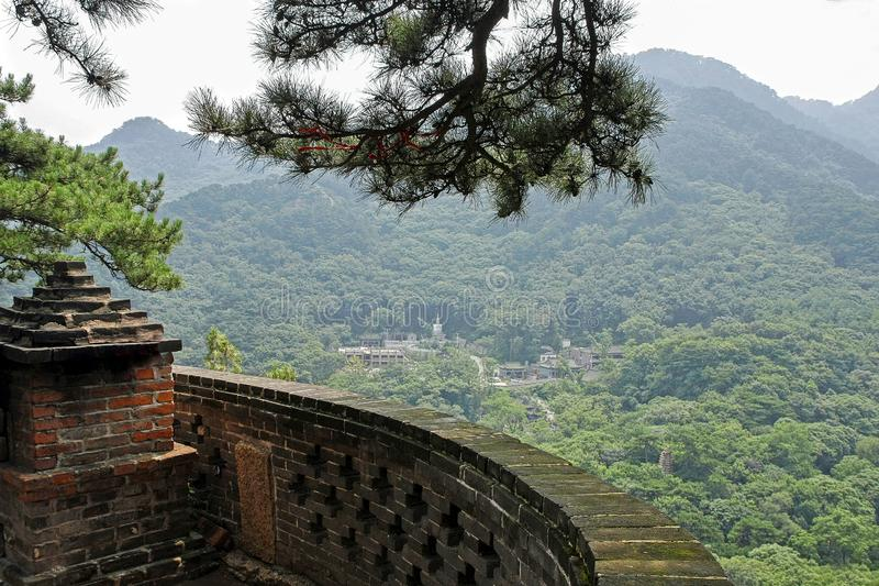 Small old monastery among mountains in China, view with barrier. Chinese landscape with fogged mountains covered with green forest, carved brick fence, branch of royalty free stock photo