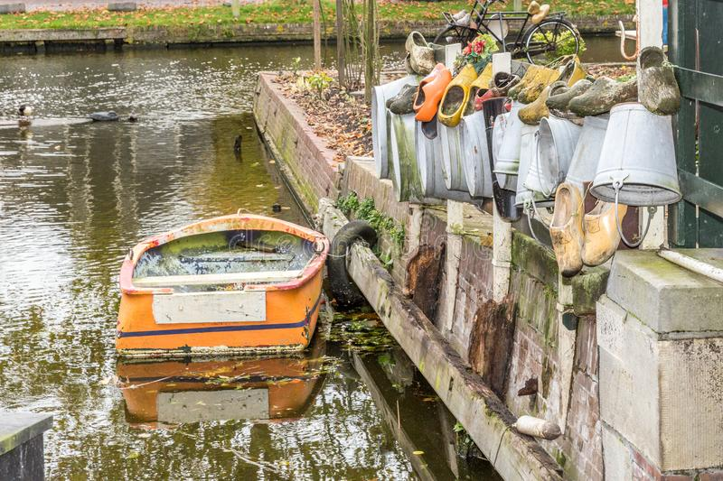 Small old orange boat in a dutch canal near to street with wooden shoes and sink buckets in different colors. Wonderful day of tourism in the Netherlands royalty free stock images
