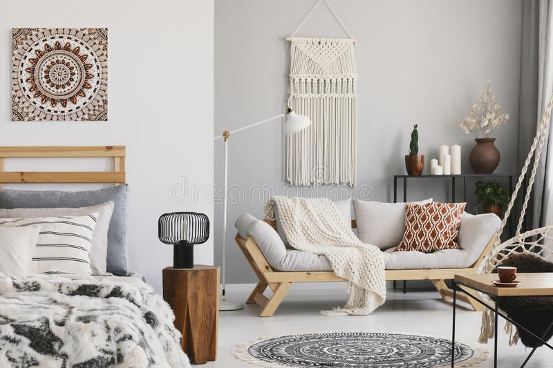 Small open space flat interior with beige sofa with cushion, macrame on the wall, rack with candles and plants and bed with. Pillows stock photos
