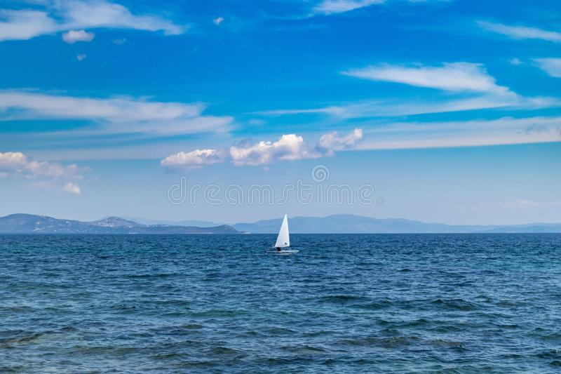 Small optimist boat with white sail, blue sky and sea background. Sailing in Aegean sea, Greece. Small optimist boat with white sail, blue sky and sea background royalty free stock images