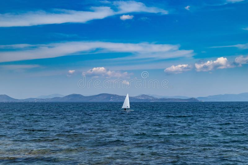 Small optimist boat with white sail, blue sky and sea background. Sailing in Aegean sea, Greece. Small optimist boat with white sail, blue sky and sea background royalty free stock photo