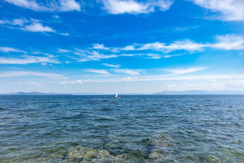 Small optimist boat with white sail, blue sky and sea background. Sailing in Aegean sea, Greece. Small optimist boat with white sail, blue sky and sea background stock photos