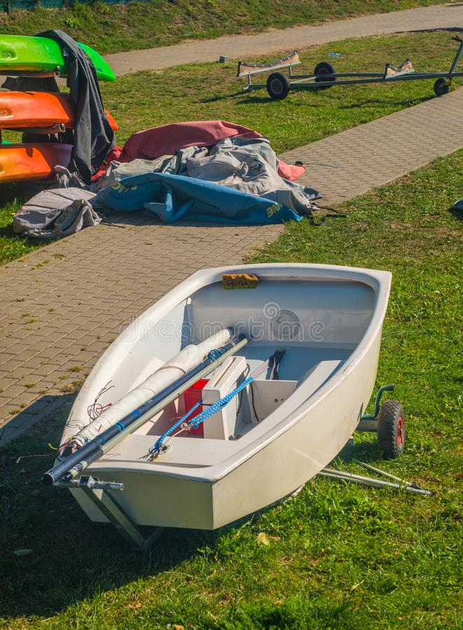 Small Optimist class boat on trailer after regatta. White hull with mast and sail inside in a cockpit of small boat of Optimist class used for training sailing royalty free stock photography