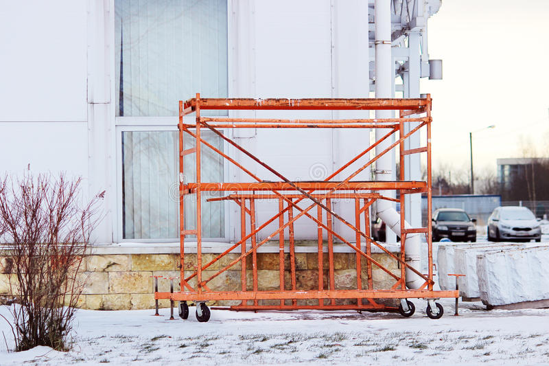 small orange building mobile work scaffolding near a large sports complex. stock image