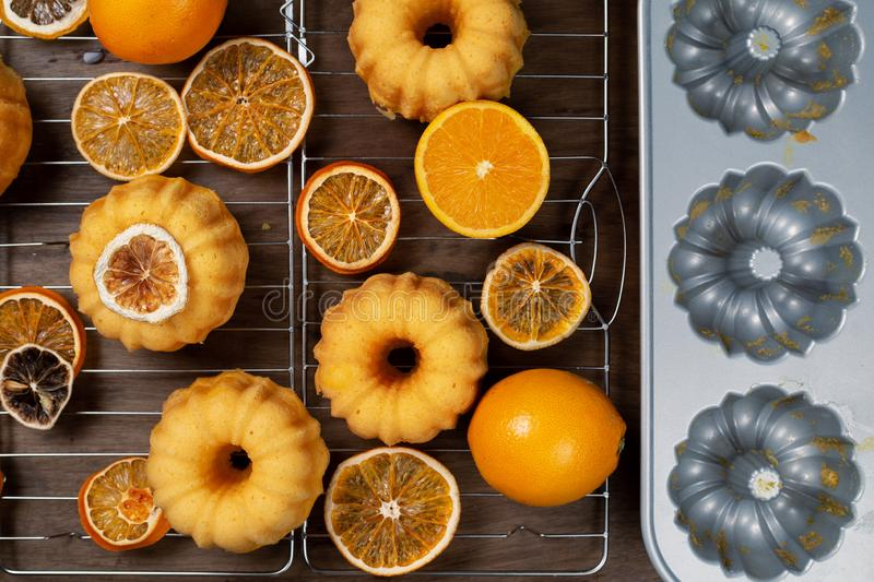 Small orange bundt cakes with fresh and dry oranges on cooling ruck, by backing mould, top view, flat lay.  royalty free stock photo