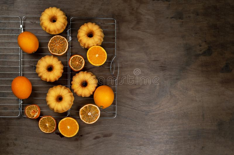 Small orange bundt cakes with fresh and dry oranges on cooling ruck, top view, flat lay.  stock images