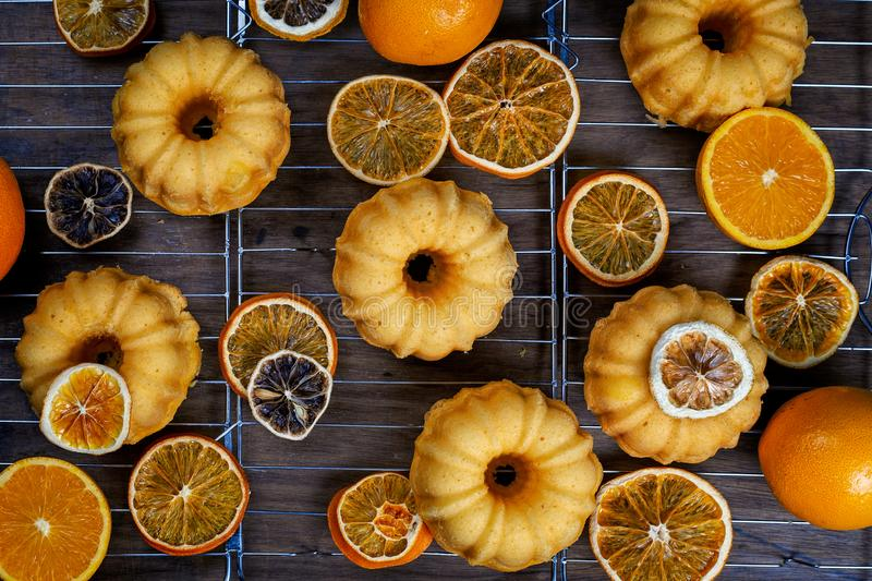 Small orange bundt cakes with fresh and dry oranges on cooling ruck, top view, flat lay.  stock photos