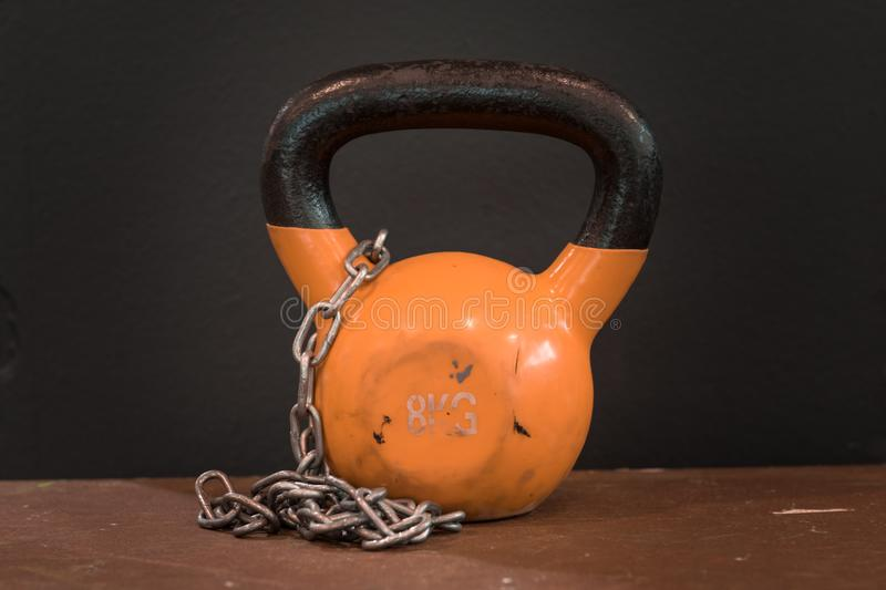 Small orange eight kilograms heavy worn out kettlebell with silver chain against black background. Gym and fitness equipment royalty free stock image