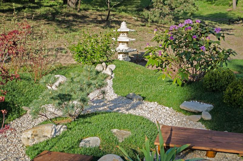 Small oriental garden for relaxing. Japanese stilb with pebble paths.  royalty free stock photography