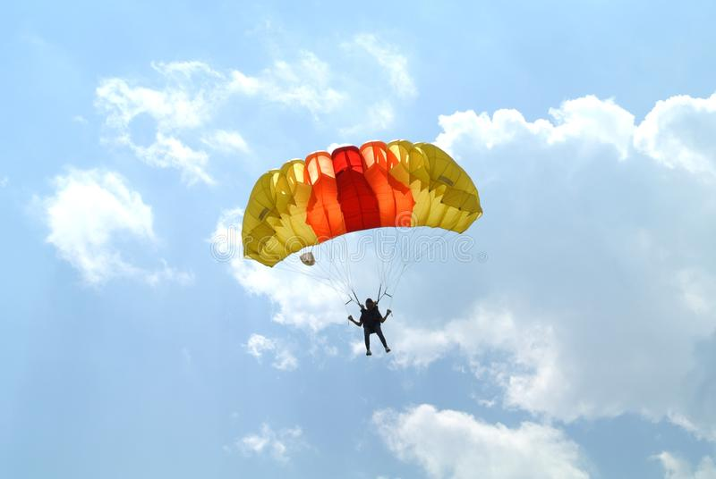 Small parachutist with colourful yelow orange red parachute on parachuting competition stock photography