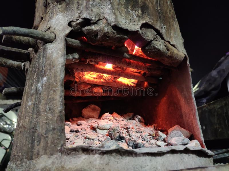 Small part of coal is burning in local Indian forge. Flame, energy, heating, cooking stock images