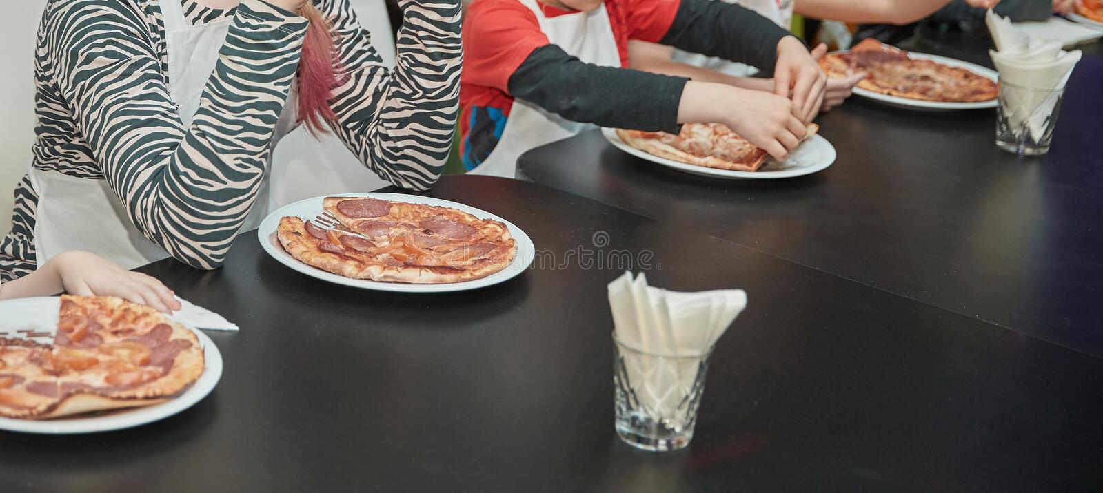 Small participants of the master class eat freshly prepared pizza. Cooking pizza together stock images