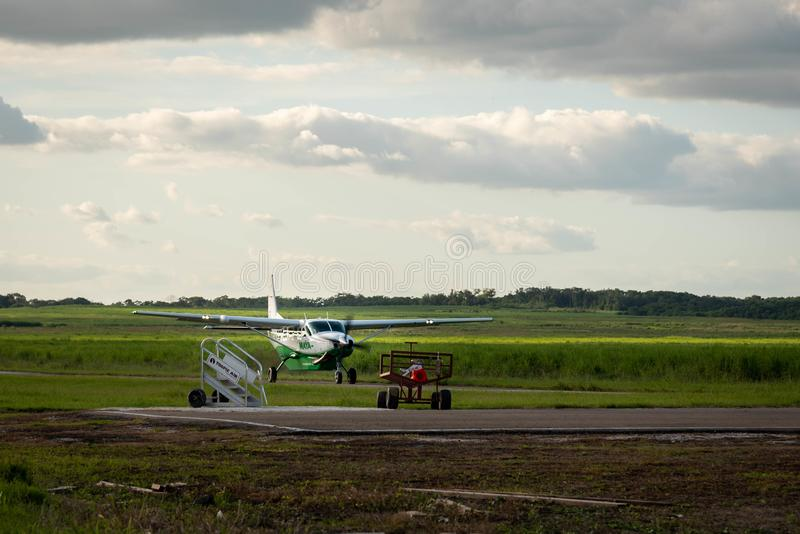 Small passenger Maya Island Air aircraft landing in  remote Orange Walk airport in the middle of the sugar cane plantation royalty free stock photos