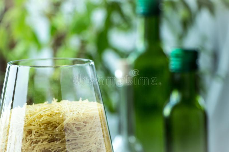 Small pasta in glass with rustic and country style background, green and white colours royalty free stock photo