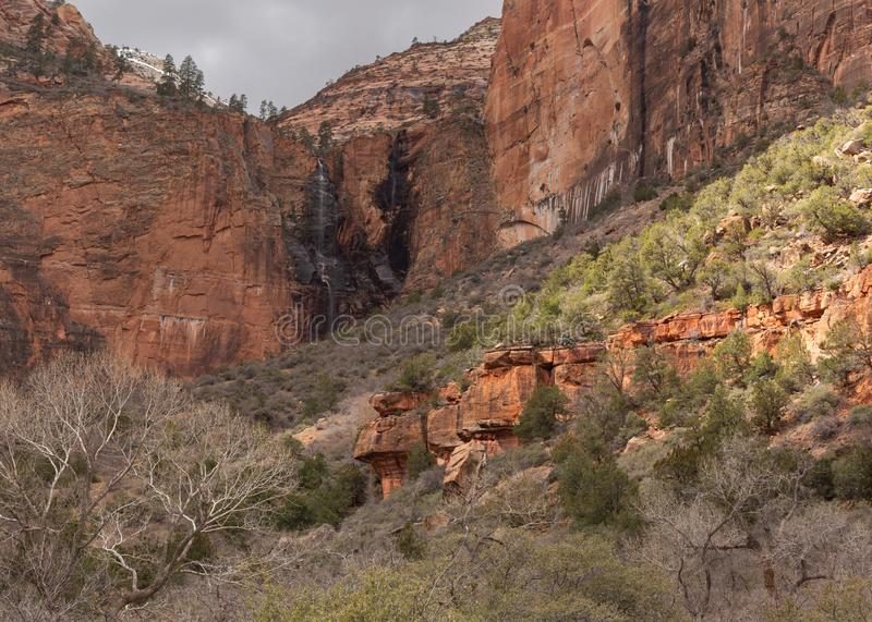 A small patch of sunshine lights the slope of the hill in the Court of the patriarchs in Zion national park Utah stock photography